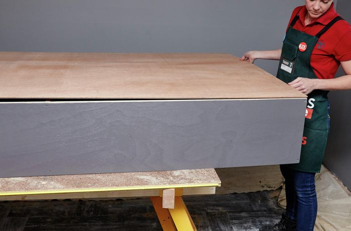 A person fitting a sheet of ply backing onto a shelving unit