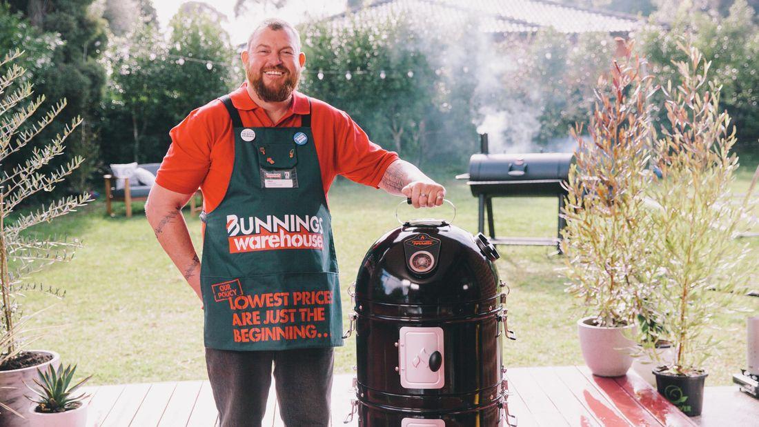 Man standing next to a bullet smoker in a backyard