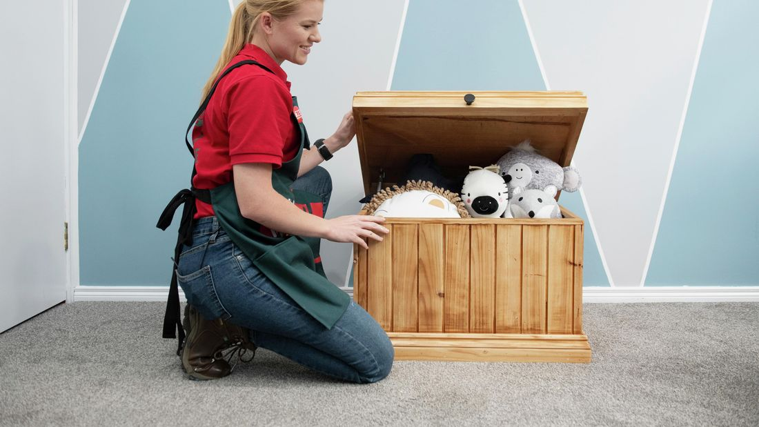 Woman opening a wooden toybox full of children's toys