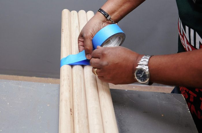 Lengths of dowel being taped together to cut bar stool legs of a matching length