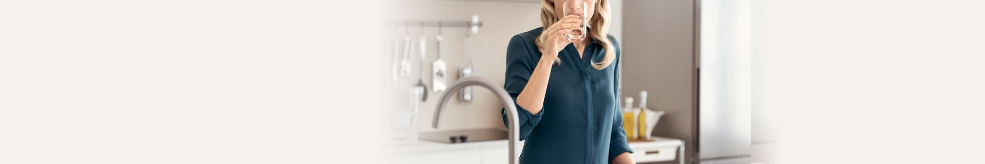 Woman drinking glass of water at kitchen bench.