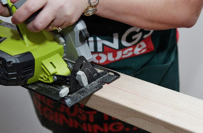 Person using circular saw to cut piece of timber.