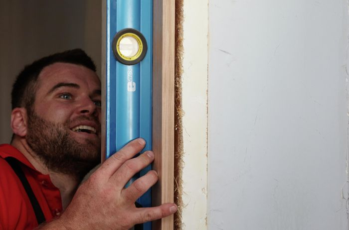 A Bunnings member with a goofy face using a spirit level to check the alignment of a new door jamb