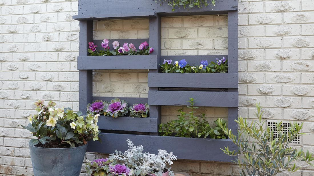 A painted timber vertical shelf with potted plants against a brick wall