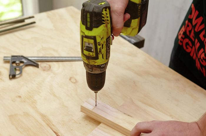 A person drilling a hole in a small piece of wood