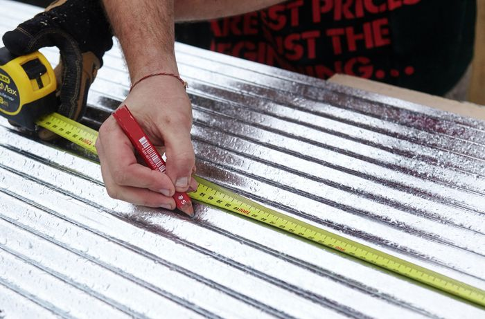 Corrugated iron being measured and marked for cutting with a pencil and tape measure