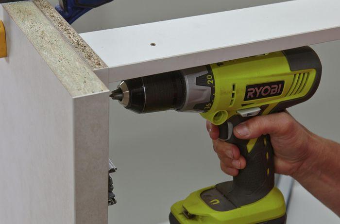 Person drilling screw into cabinet