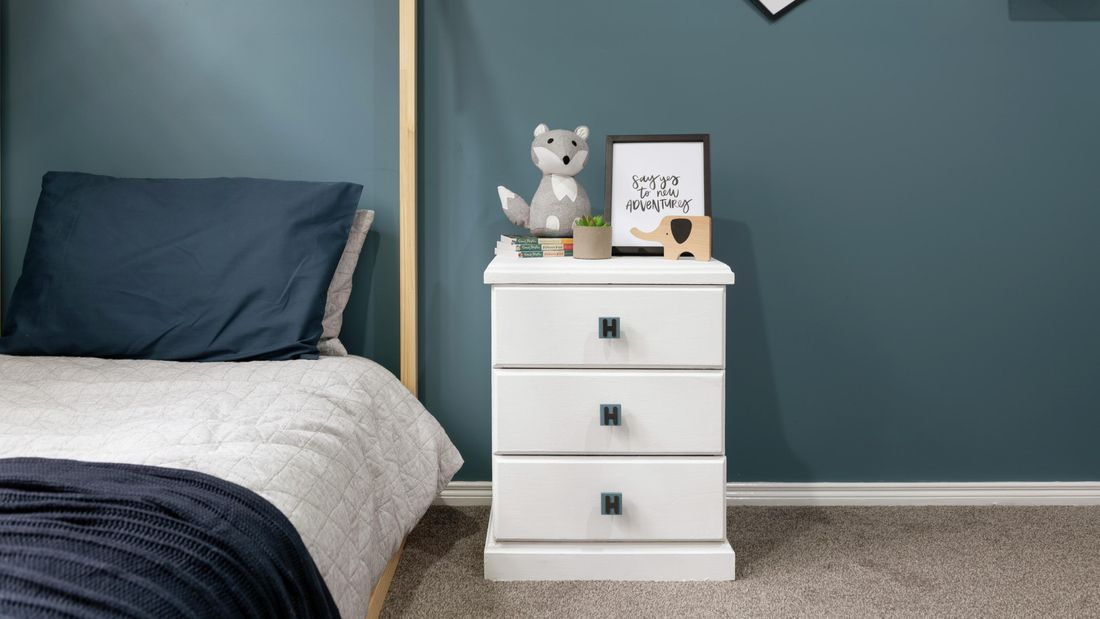 A white chest of drawers with handles customised with the letter H, in a blue themed bedroom setting