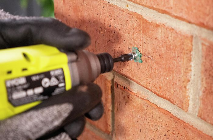 Person drilling screws into brick wall and plug.