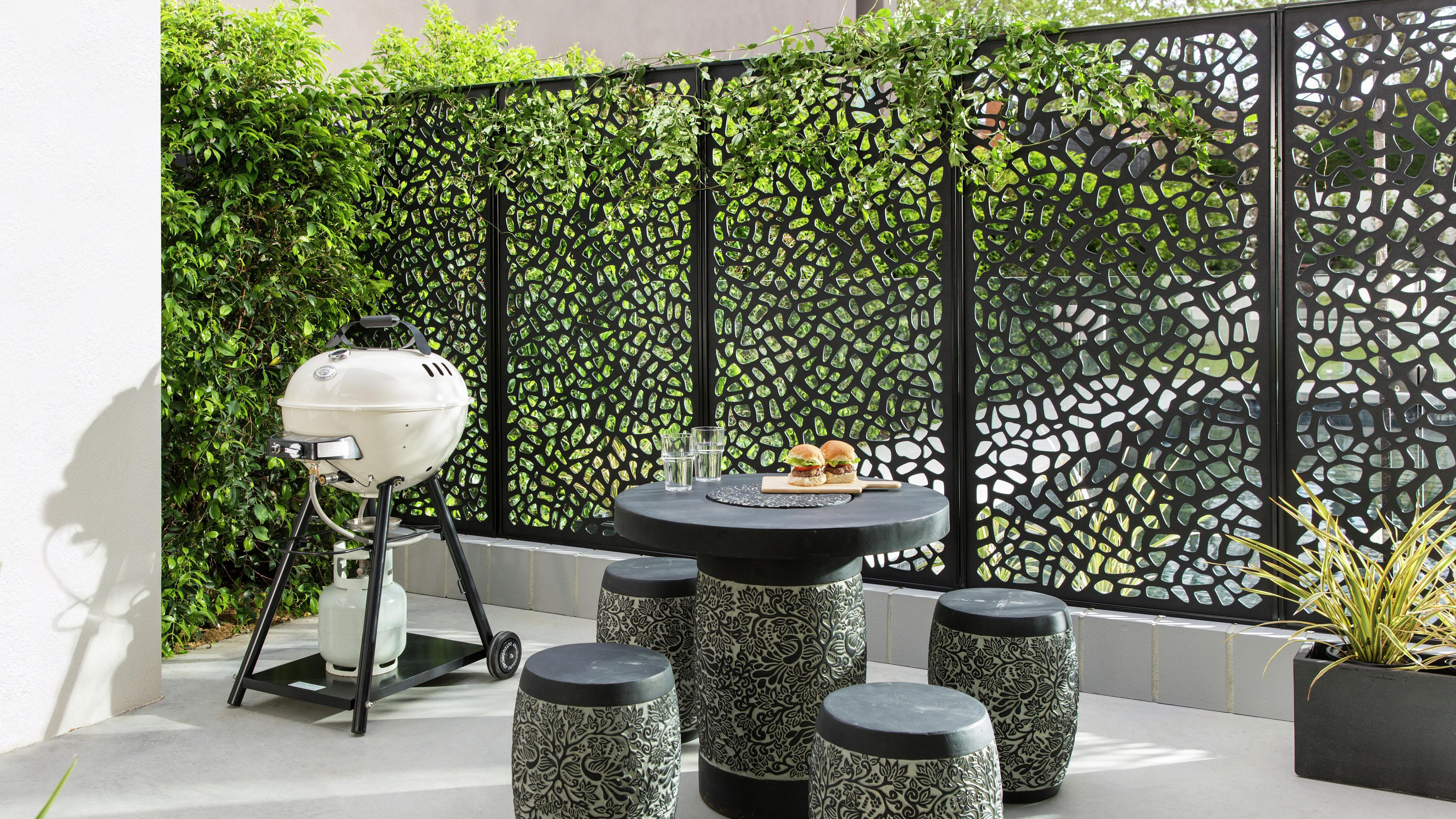 Outdoor dining setting with kettle BBQ, and plant-covered privacy screens.