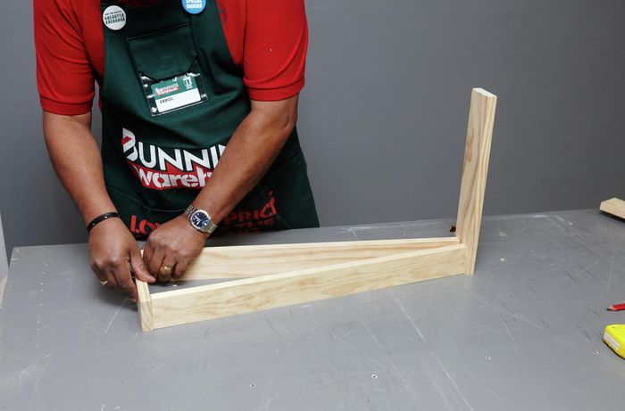 A person fitting a bottom piece of timber to A-frame legs