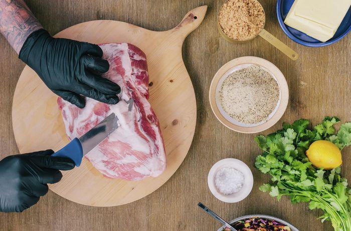 Person trimming fat off a pork shoulder