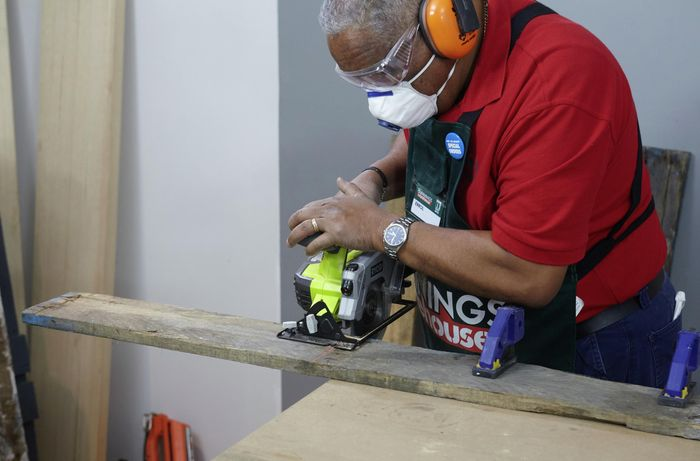 A person wearing protective gear cutting a length of timber using a circular saw