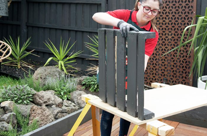 Part of a pallet being painted Bunnings teal
