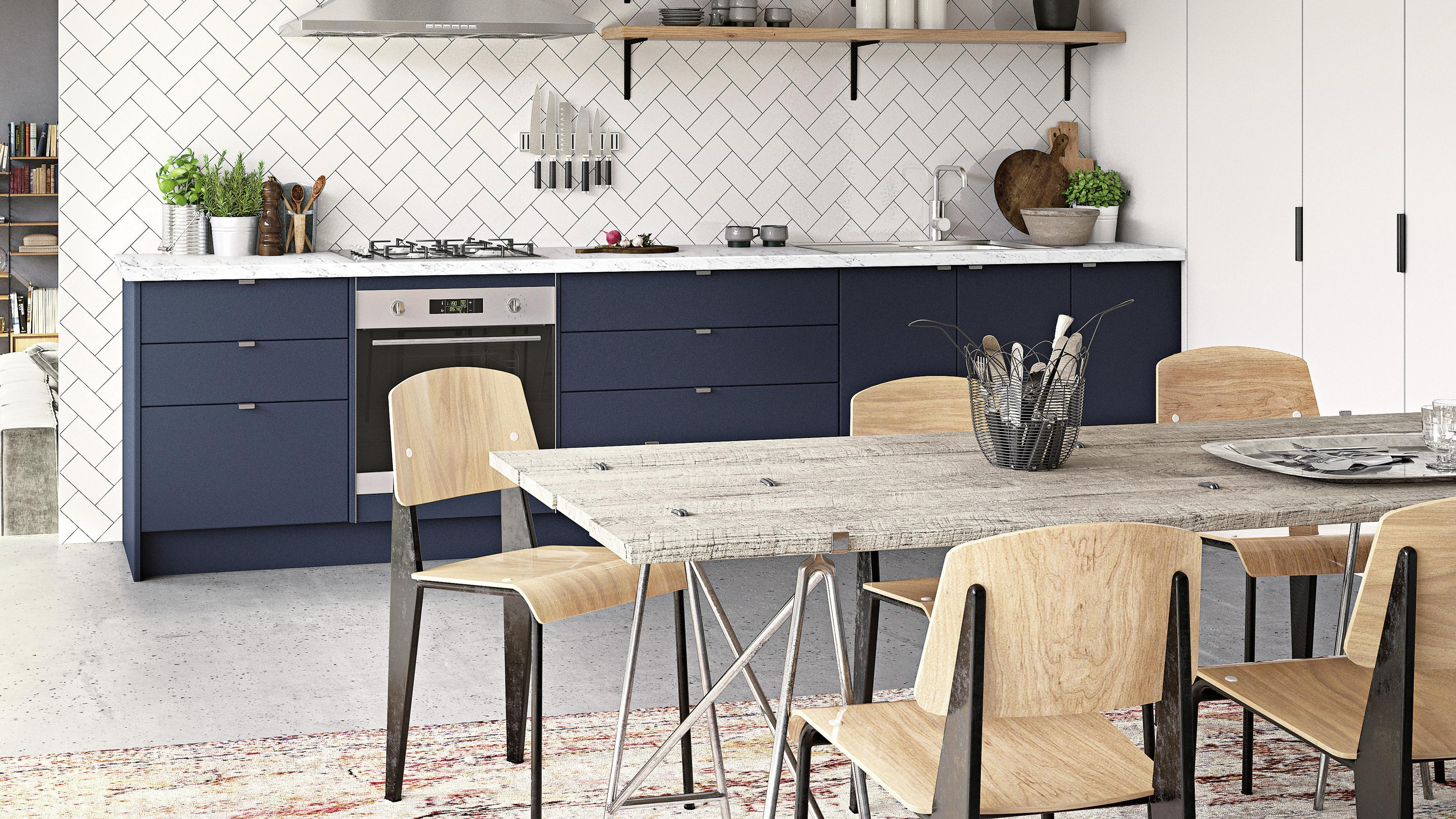 Kitchen featuring navy cabinetry, marble benchtop and subway tiled splashback.