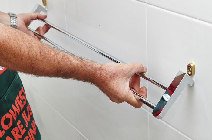 A person attaching a towel rail onto fittings attached to a tile wall