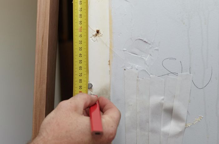 A bare wall being measure for a replacement door jamb