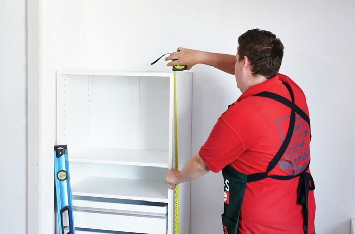 Person measuring height of wardrobe insert unit shelving.