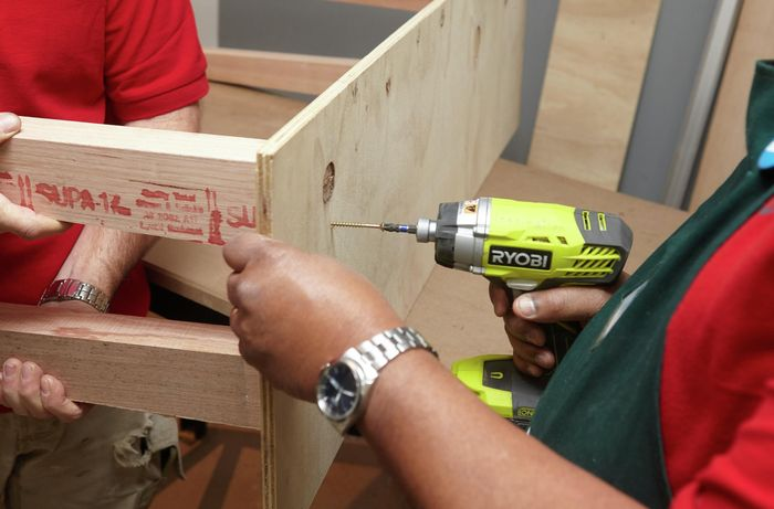 Person drilling timber legs onto ply panel