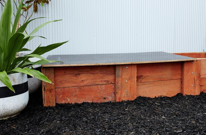 A completed sleeper compost bin sitting amongst dark tanbark in front of a corrugated iron wall