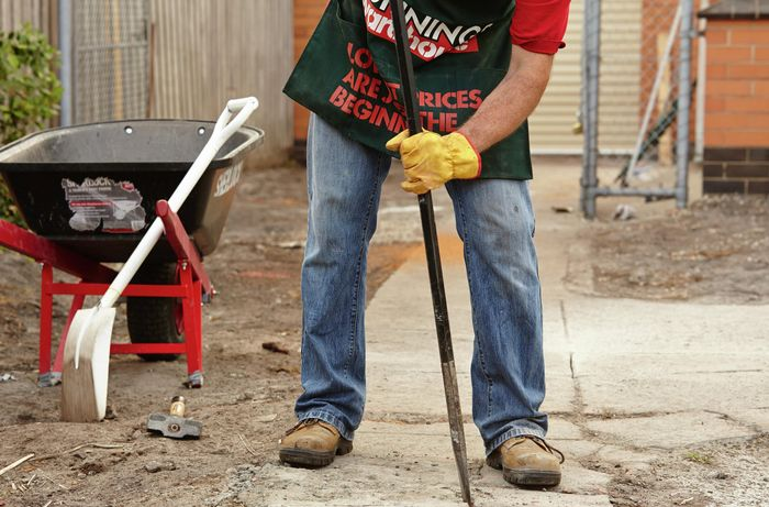 Bunnings team member using a fencing bar to pry concrete from the ground