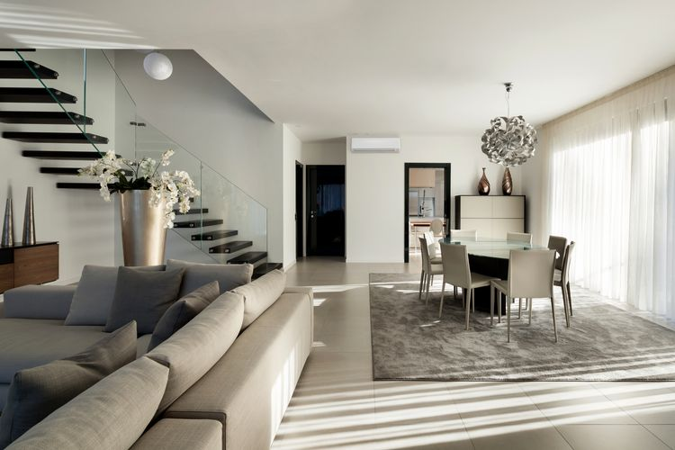 Lounge and dining room with grey couch. glass-topped dining table and grey carpet