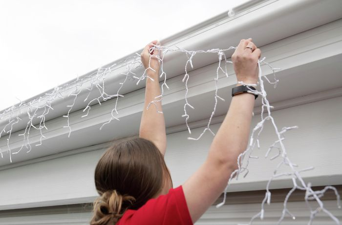 A person reaching up to attach a string of lights to gutter hooks