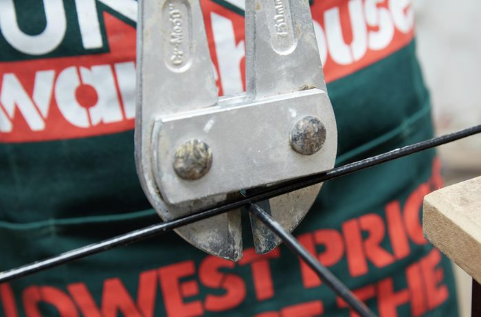 Wire mesh being cut with a pair of bolt cutters