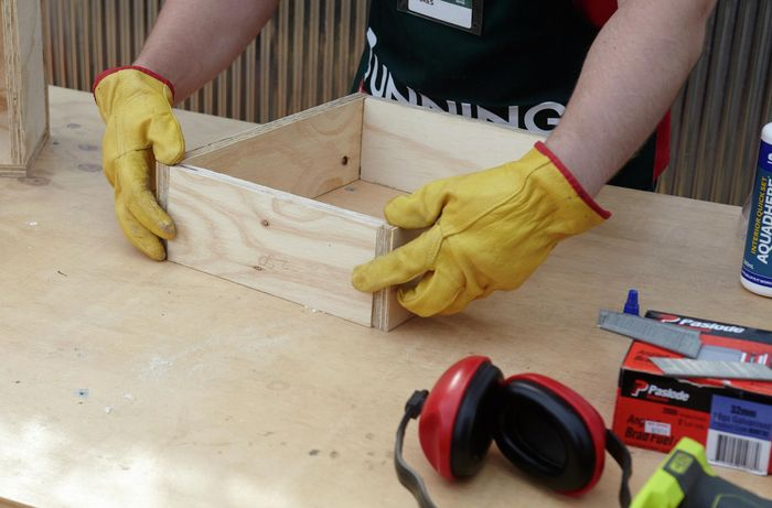 Person assembling pieces of timber into rectangle