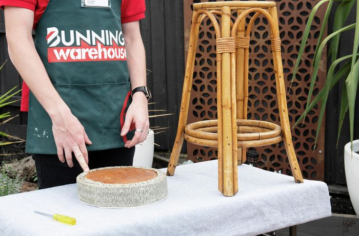 Person standing next to cane bar stool with seat removed on a work bench
