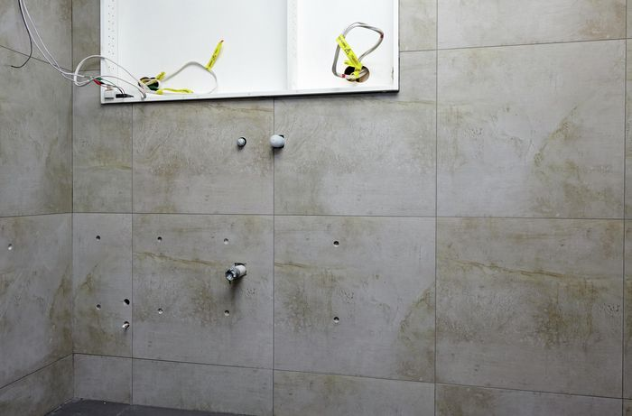 A tiled bathroom wall with holes drilled and pipes capped off
