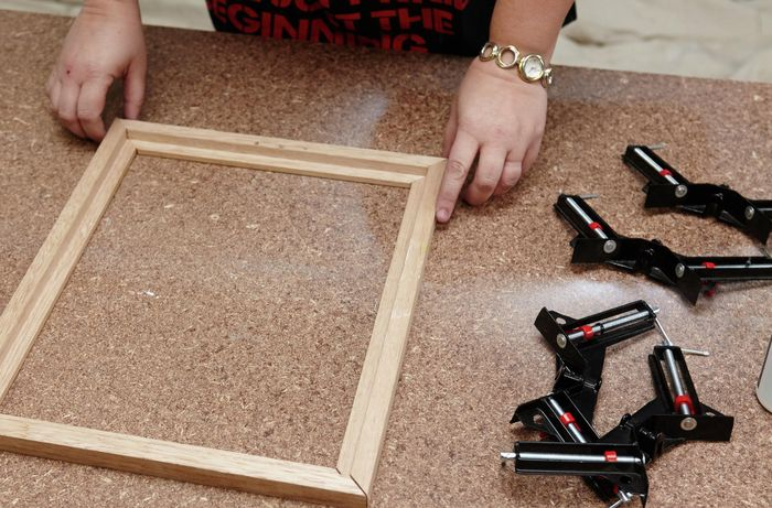 Four panes of a picture frame laid out on a workbench, next to a series of corner clamps