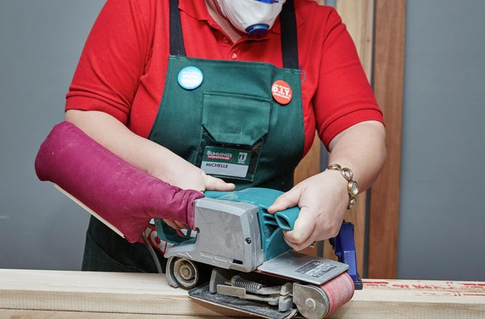 Person using a power sander on bit of timber.