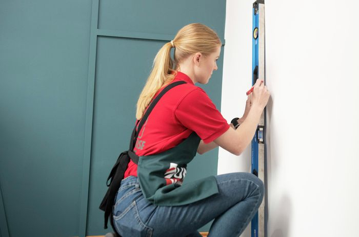 Person using spirit level to mark up wall.