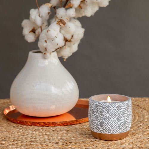 A lit candle under a potted cotton branch