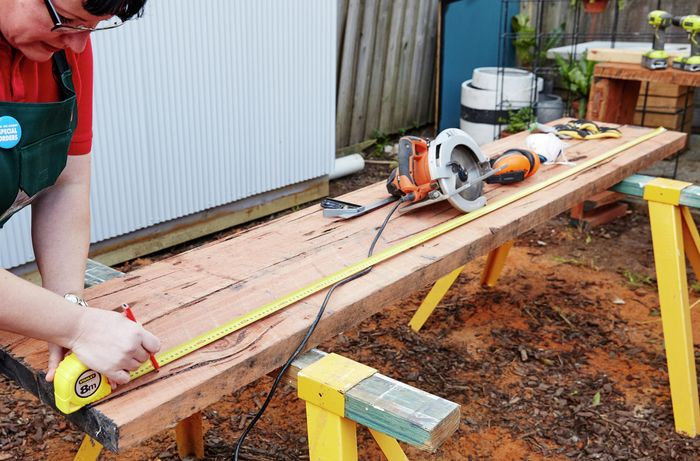 A length of sleeper being measured and marked for cutting with a tape measure and pencil, with a circular saw sitting in the background
