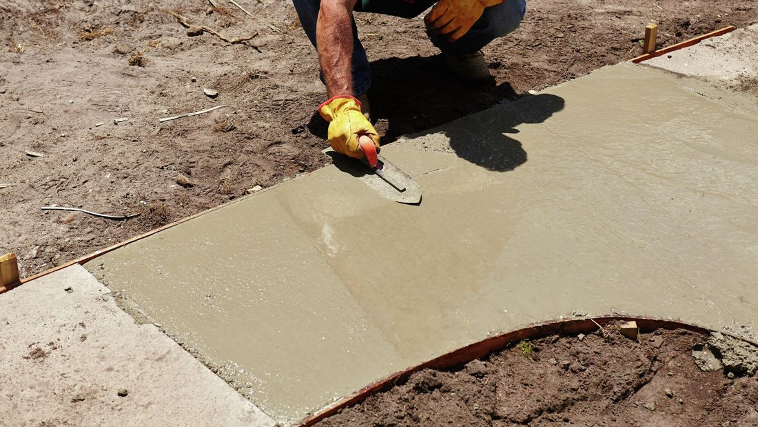 Gloved person smoothing wet concrete with a straight edge