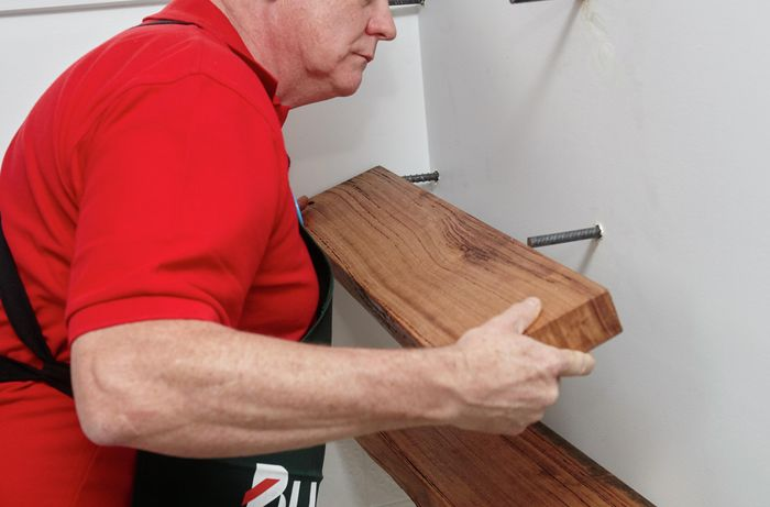 Long screws sticking out of a wall and a person about to slide a timber shelf with holes onto them.