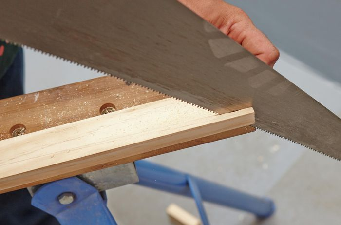 A person sawing down the length of a piece of timber using a hand saw