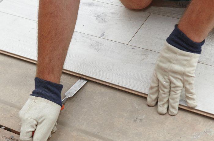 Person removing laminate flooring.
