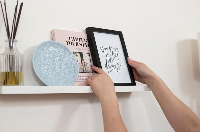 Wall-mounted shelf with a book, plate, vase and photo frame