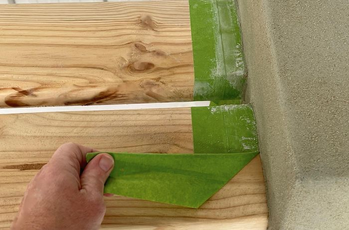 A person peels painter's tape off timber slats]