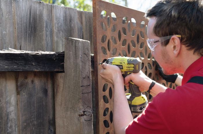 A person fixing a steel screen to a paling fence using a cordless drill