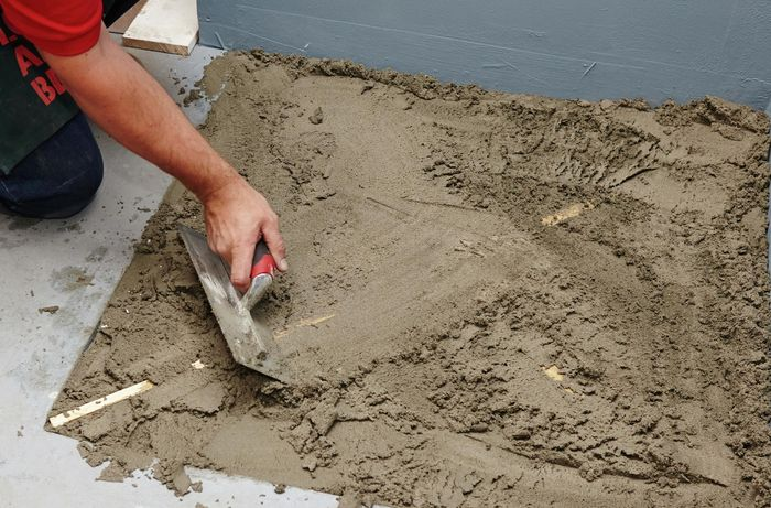 A person using a flat trowel to spread screed across a shower base