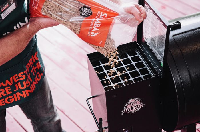 Person pouring pellets into the hopper of a pellet smoker