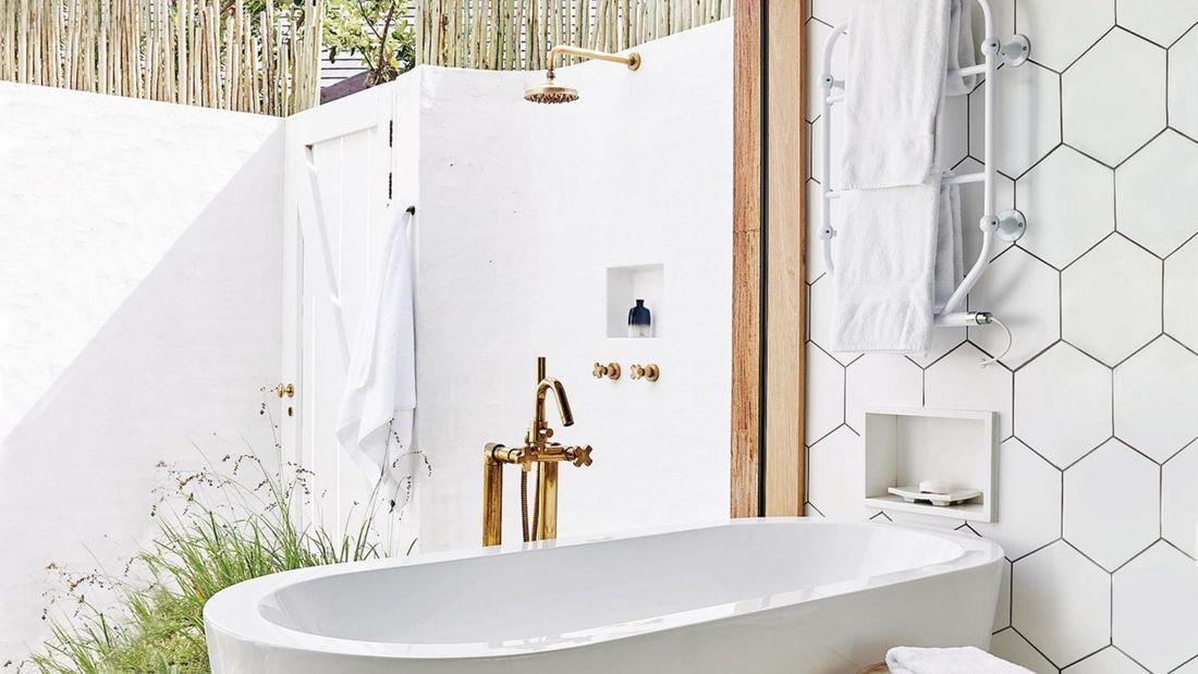 White modern bath with a brass outdoor shower.