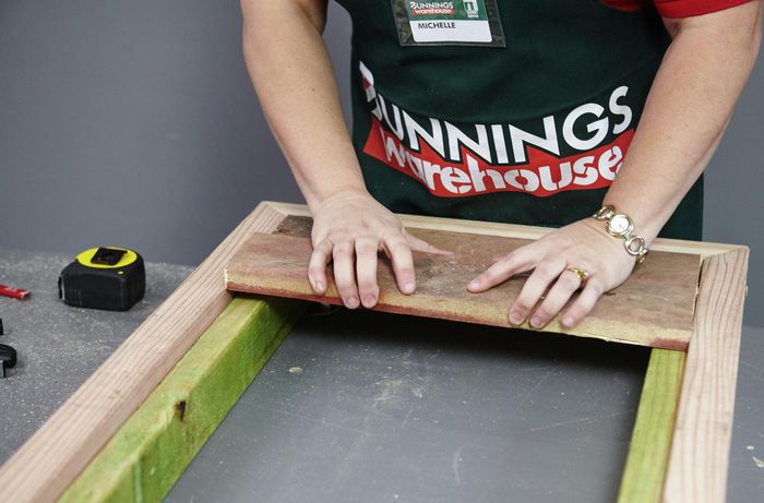 Planks being laid into a wooden frame