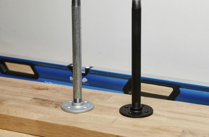Two metal pipe shelf supports, one spray painted black