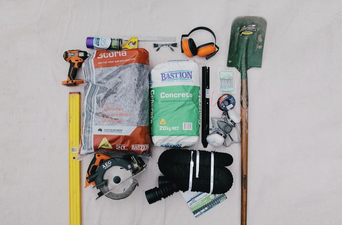 Level, drill, safety equipment, saw, shovel, and other tools and materials, laid out on the ground.