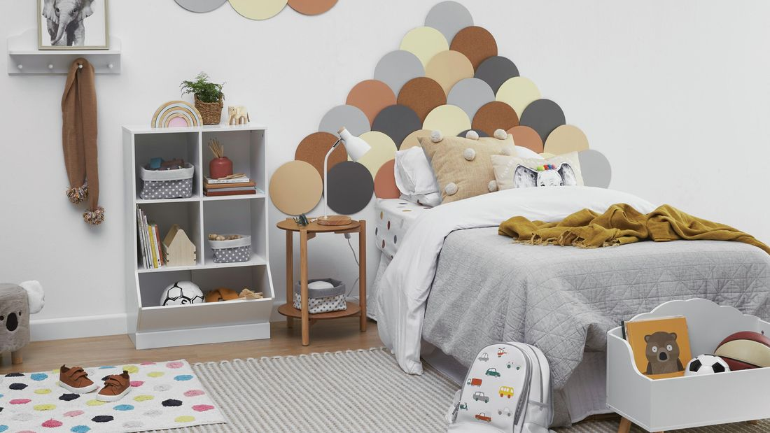Kids bedroom with colourful bedhead, cube storage and lots of toys.